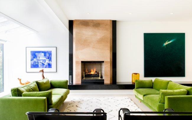 carnarvon street living room with dual forest green sofas and fireplace